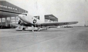 C-39 aircraft with 6th Fighter Squadron emblem in front of hangars at Hickam Field, c1940.