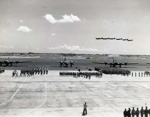 Mass awards ceremony at Hickam Field in which 7th Air Force awarded medals to fliers who participated in Battle of Midway. Flying overhead are P-40E aircraft. Parked on flight line are B-17s on each side of a Martin B-26, September 17, 1942.