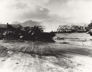 Wrecked planes on Wheeler Field flight line with Hangar 2 in background and tent quarters where many enlisted men were killed, December 7, 1941.