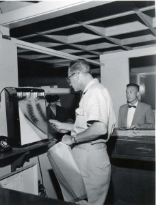 U.S. Health Inspector reads an x-ray before admitting traveler into the U.S. at Honolulu International Airport, 1950s.