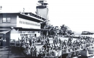 Passengers crowd the fence waiting for arriving passengers at Honolulu International Airport, 1950s.
