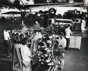 Hawaiian Airlines mechanics work on engines in shop at Honolulu International Airport, 1950s.