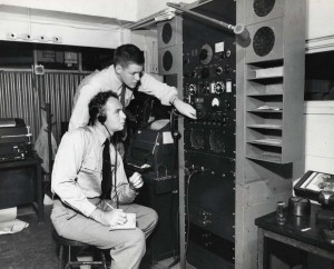 Hawaiian Airlines pilots at Honolulu International Airport listen to weather information before their flight, 1950s.