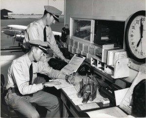 """Hawaiian Airlines. pilots. J. F. """"Deke"""" Carr, seated, and R. S. Barnes, standing check flight information at Honolulu International Airport, 1950s."""