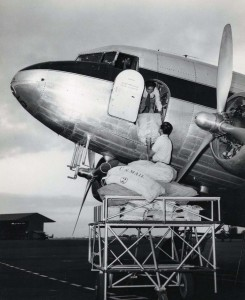 Air mail is loaded onto a Hawaiian Airlines plane at Honolulu International Airport, 1950s.