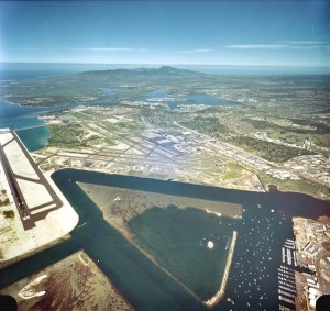 Reef Runway at left, Keehi Lagoon and South Ramp, bottom, Honolulu International Airport in center and Hickam Air Force Base and Pearl Harbor at top, January 1, 1982.