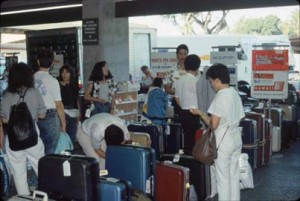 Travelers exit International Arrivals Building into Group Tour Area, Honolulu International Airport, 1990s.