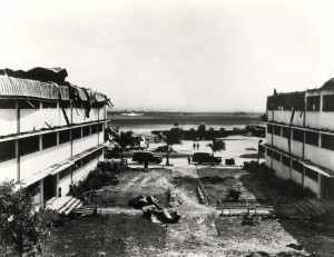 Looking out toward Hangar Avenue and the flight line from coutyard between heavily damaged Wing E and Wing D of the big barracks at Hickam Field, December 7, 1941.