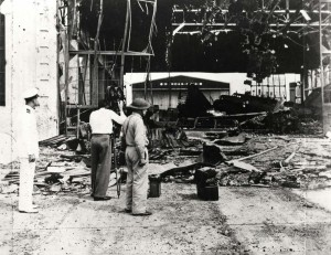 Inspecting Hickam Field Hangar 1 damage, December 7, 1941. A 5th Bombardment Group B-18 aircraft can be seen in background at right.