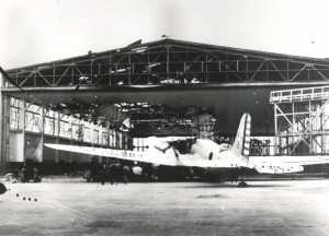 A B-18 belonging to 11th Bombardment Group outside of wrecked hangar at Hickam Field, December 7, 1941.