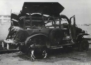 Heavily damaged truck at Hickam Field parked next to parade grounds with big barracks in background, December 7, 1941.