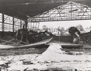 Close up view of wreckage in Hangar 1 at Wheeler Field, December 7, 1941. A P-26 aircraft is on left with a P-40 in background.
