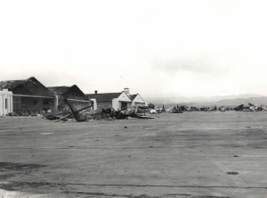 Aircraft wrecked on Wheeler Field flight line, December 7, 1941. In front is a demolished amphibian plane.