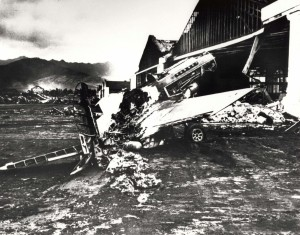 Severely damaged fighter plan sits in the midst of rubble in front of a burned out hangar at Wheeler Field, December 7, 1941.